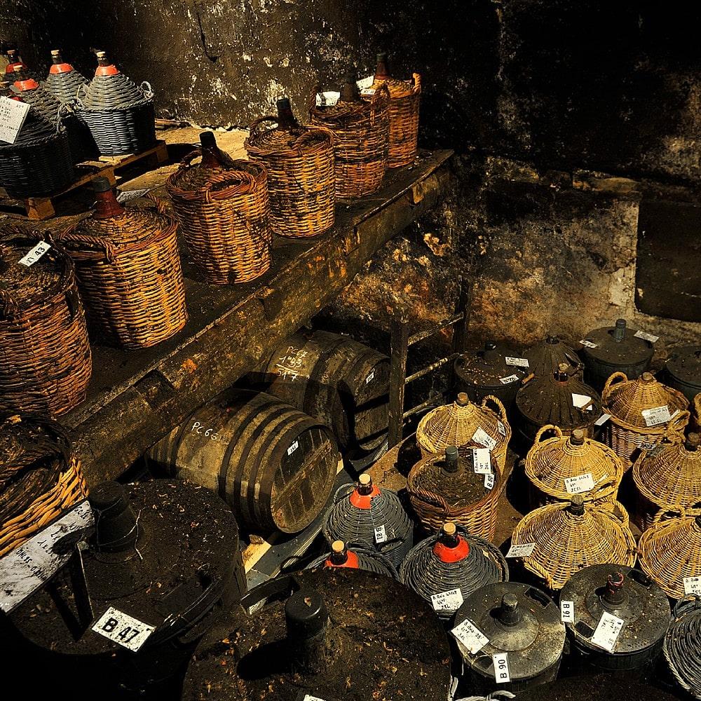 Vintage Cognacs in Flaschenkörben.